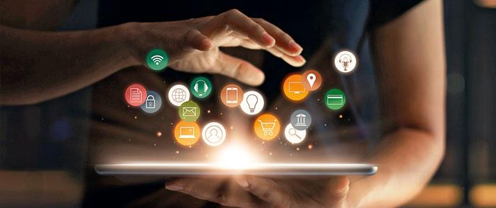 Über einem leuchtenden Tablet schweben verschiedene digitale Symbole. Ein Person hält das Tablet mit einer Hand vor sich, eine andere Hand schwebt über dem Tablet.